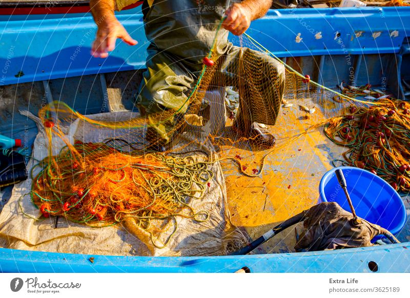 Fisherman is empty fish from net in his small boat Angling Arrange Boat Boot Bunch Buoy Catch Cork Drag Effort Empty Entrap Equipment Fabric Fish Out Fishery