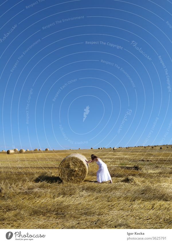 Woman Pushing Hay Bale Hay bale Bale of straw rolling Clear sky Meadow Field Harvest Grain Straw white dress Summer Agriculture