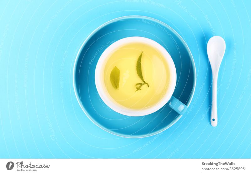 Blue cup of green oolong tea over blue background Tea yellow herbal spoon white saucer paper pastel closeup elevated top view high angle directly above hot