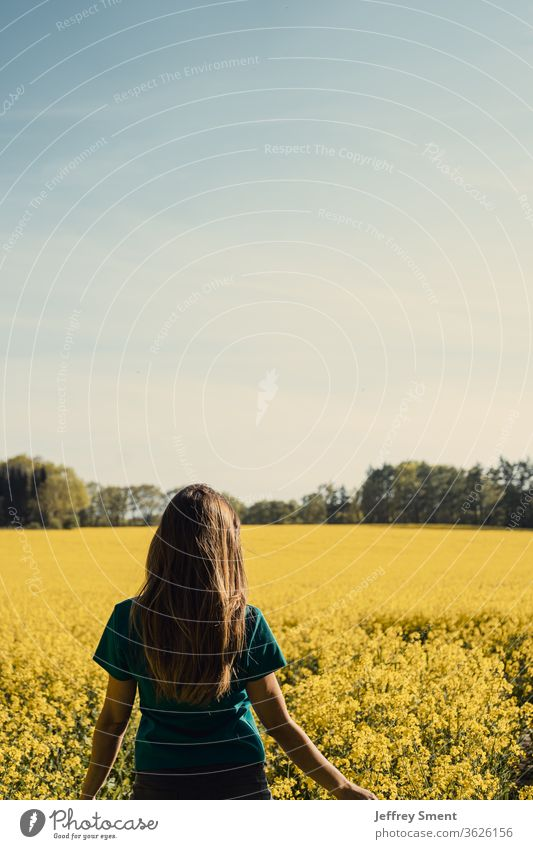 Woman in a rape field Canola Canola field Oilseed rape flower spring Freedom Nature bleed flavor Lanes & trails hike sunny day
