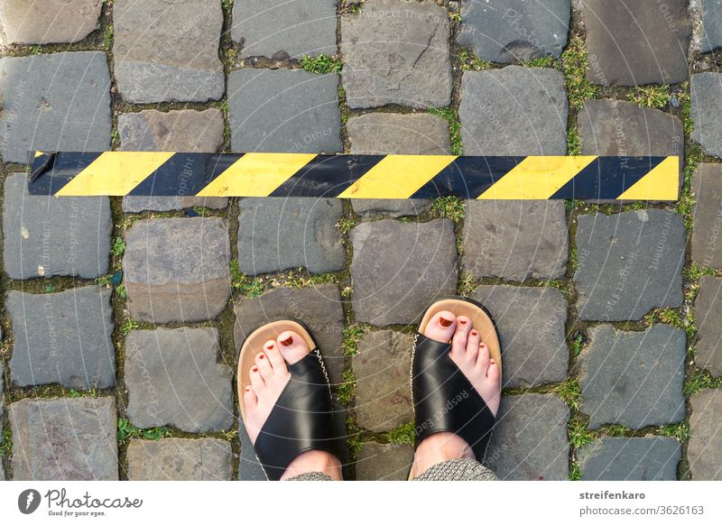 Keep your distance! - female feet stand in front of a black and yellow tape on cobblestone gap keep sb./sth. apart corona Corona virus Protection pandemic
