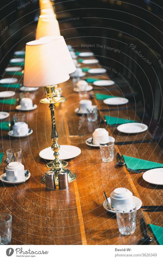 a set table / blackboard with empty seats Empty corona gap Table Blackboard Revealed covered Crockery Lamplight lamps Invitation meetings Business void