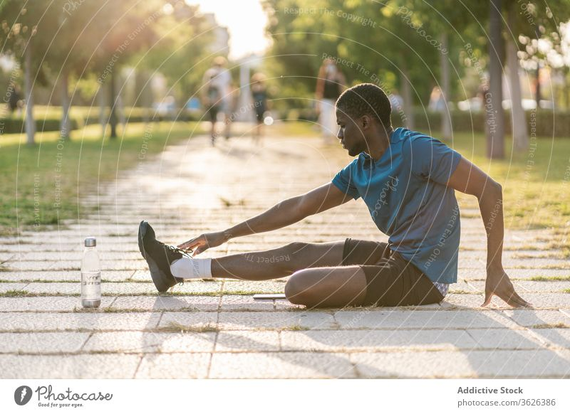 Athletic black man exercising at the park male fitness workout sport runner warming up flexibility healthy lifestyle stretching athlete young training body