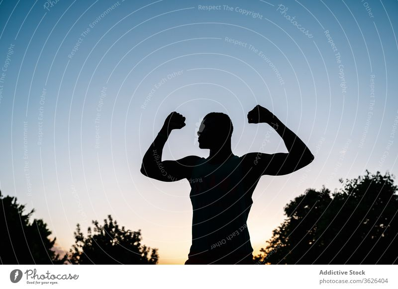 Athletic black man exercising at the park african muscular silhouette fitness strong flexing body muscle biceps arms athlete strength lifestyle chest athletic