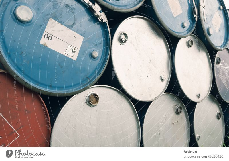 Old chemical barrels. Blue and purple oil drum. Steel oil tank. Toxic waste warehouse. Hazard chemical barrel with warning label. Industrial waste in metal drum. Hazard waste storage in factory.