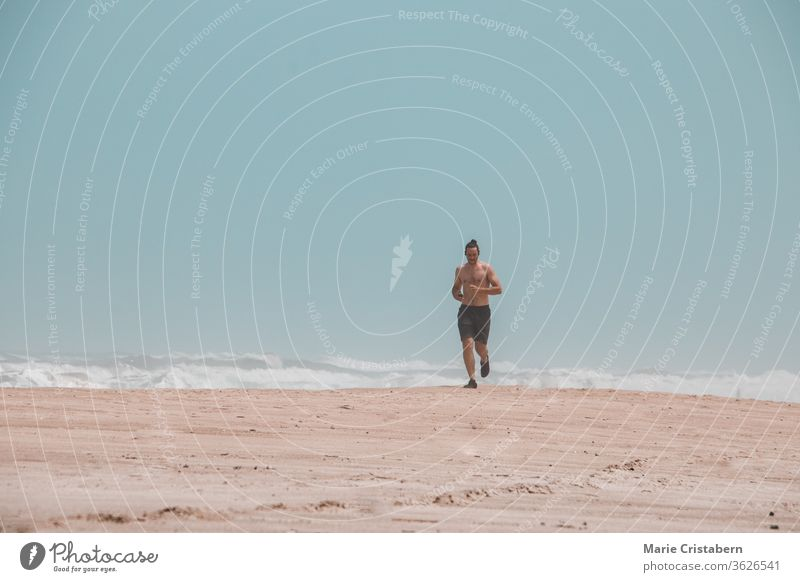 Jogging alone on the beach shows the new normal style of fitness during the covid-19 pandemic jogging exercise running active lifestyle healthy lifestyle