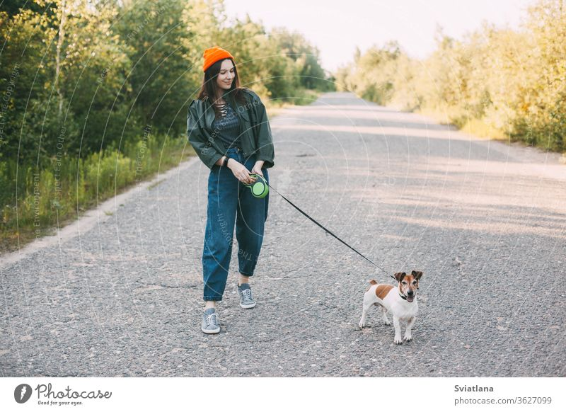 Cute modern teen girl in a green jacket and orange hat walks with her dog in nature. Pet, care, friendship. park young walking woman animal pet summer outdoor