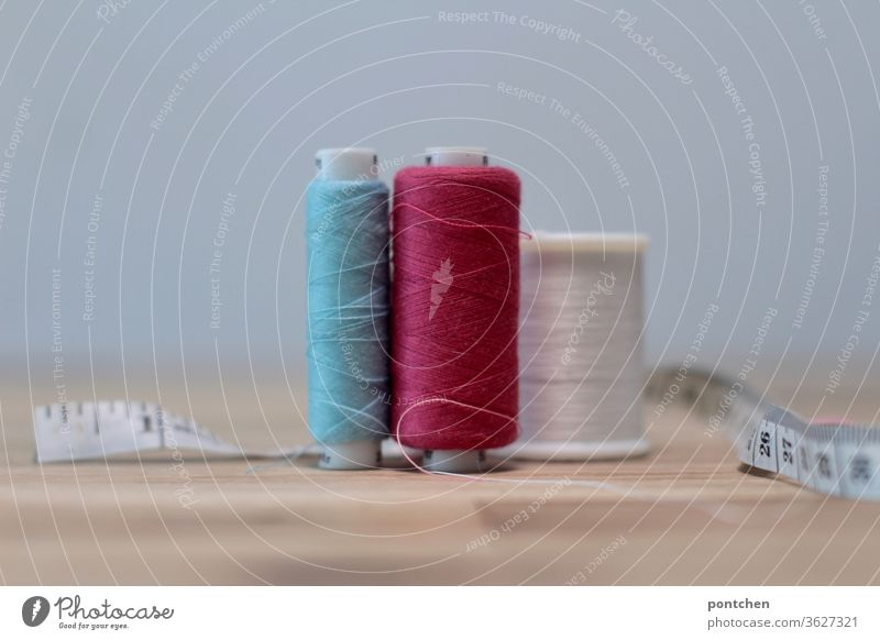 Sewing threads in different colours and a measuring tape on a table. Craft, sewing. Tape measure Craft (trade) do needlework DIY doityourself colors Handcrafts