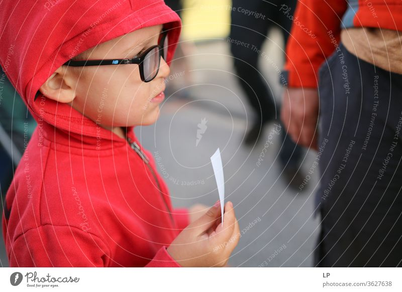 child with a ticket waiting in line Child Ticket Wait Loneliness Think Sadness lonely Exterior shot Transport Exchange of information Information Communicate