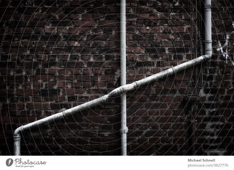 Crossing water pipes on an old brick wall of a house reeds Water pipes Transmission lines Wall (building) Deserted Wall (barrier) Metal Colour photo Old