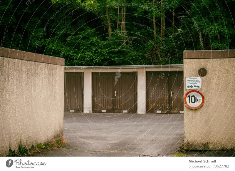 Old garages in a garage yard in front of a forest area Garage Brown Gloomy slow down Exterior shot Colour photo Deserted