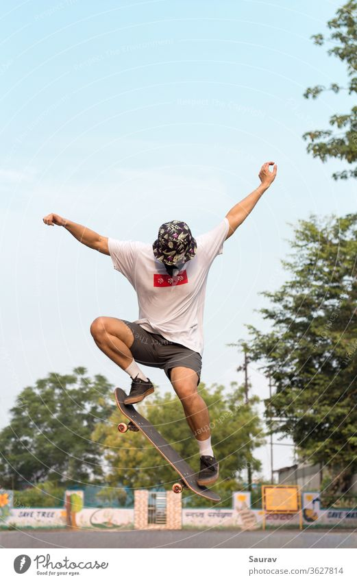A Young Adult wearing a protective mask to avoid Coronavirus infection while doing an Ollie stunt on his Skateboard outdoors ion an empty road. summer