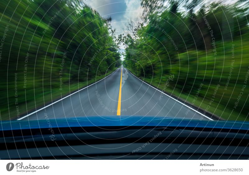 Front view of blue car driving with fast speed on the middle of asphalt road with white and yellow line of traffic symbol in the green forest. Trees beside the road is blurred. Car with blur motion.