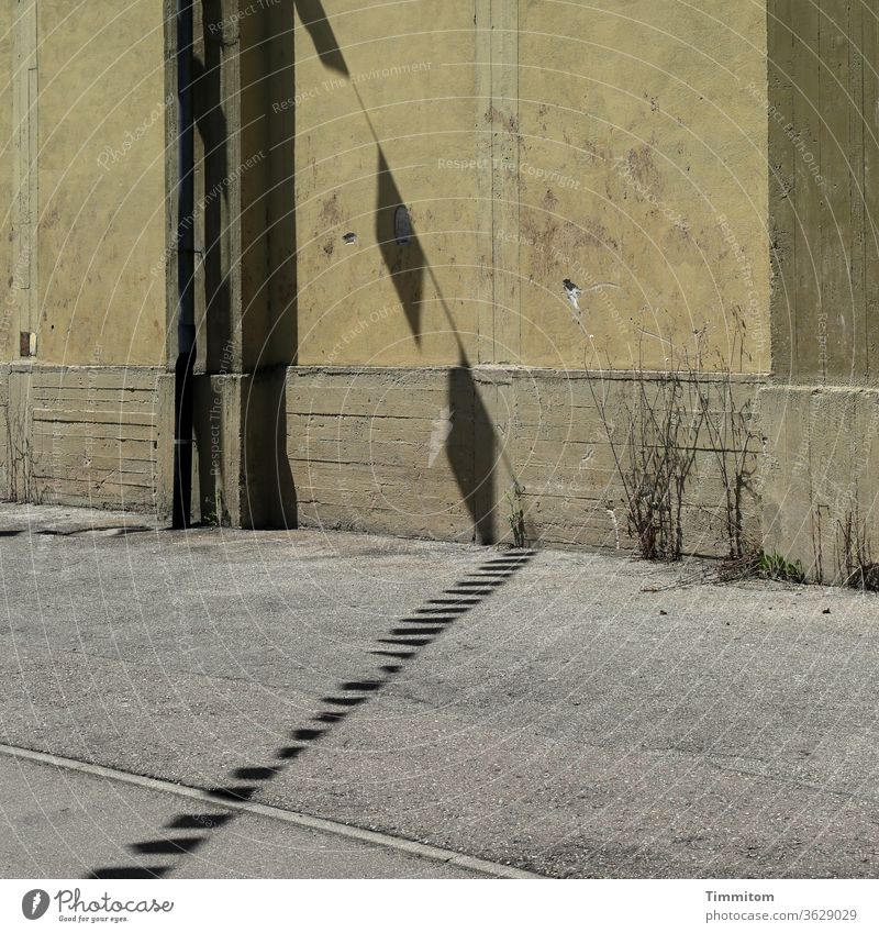Old industrial building with street and cheerful pennant shadow Industrial building Wall (building) Shadow pennant chain Asphalt Street Flag lines Concrete