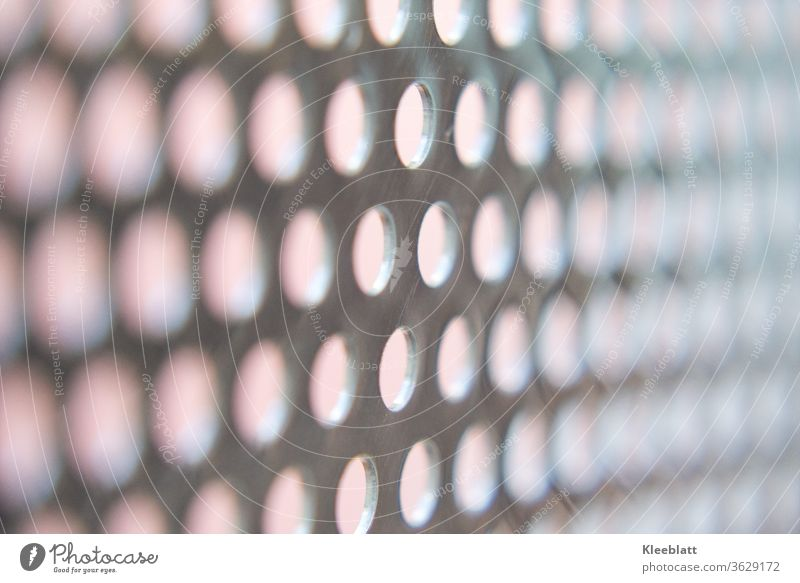 Stainless steel perforated plate with bright background, clear focus in the middle of the picture, right and left blurred Perforated plate, Hollow Metal Pattern