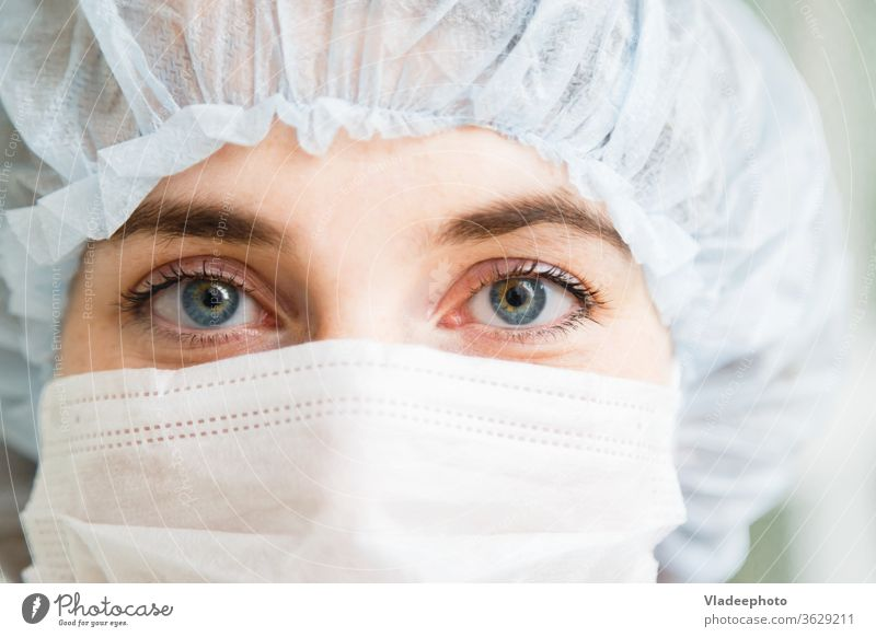 Close-up portrait of young female surgeon doctor or intern wearing protective mask and hat medical surgery concept emergency hospital work nurse care health
