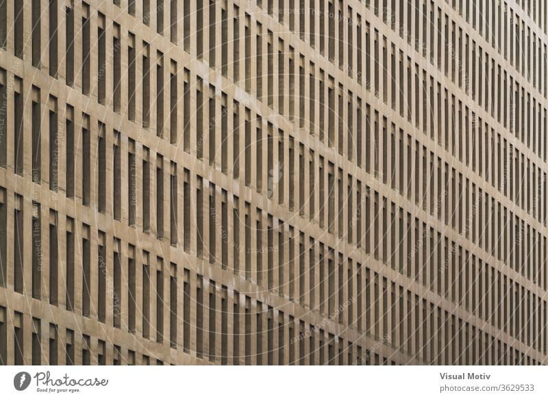 Uniform facade of an office building with rows of vertical windows structure architecture urban metropolitan abstract color exterior repetition pattern outdoors