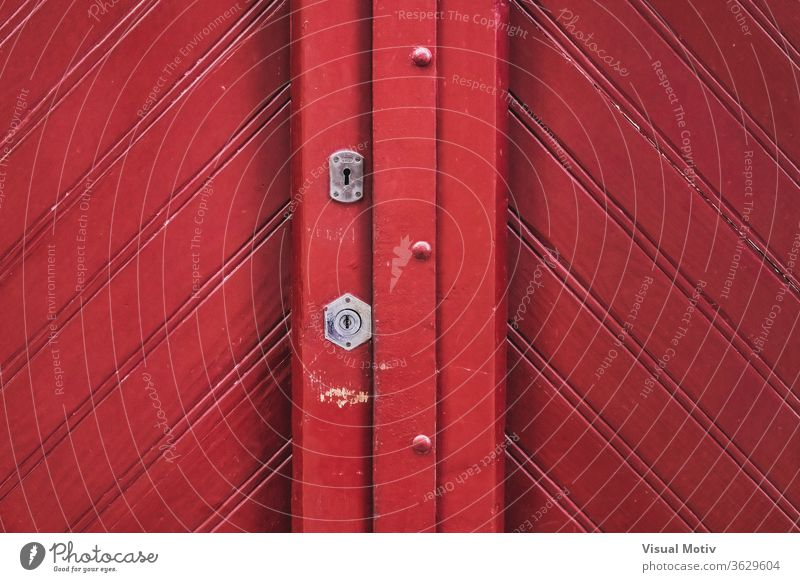 Detail of a traditional vintage red wooden door shape keyhole lock geometry design architecture entrance detail structure exterior material weathered texture