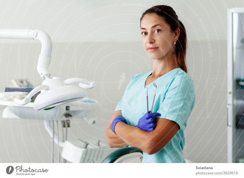 A female dentist is sitting in a chair and smiling while holding tools in her hands. dentistry office care clinic doctor equipment health hygiene medical