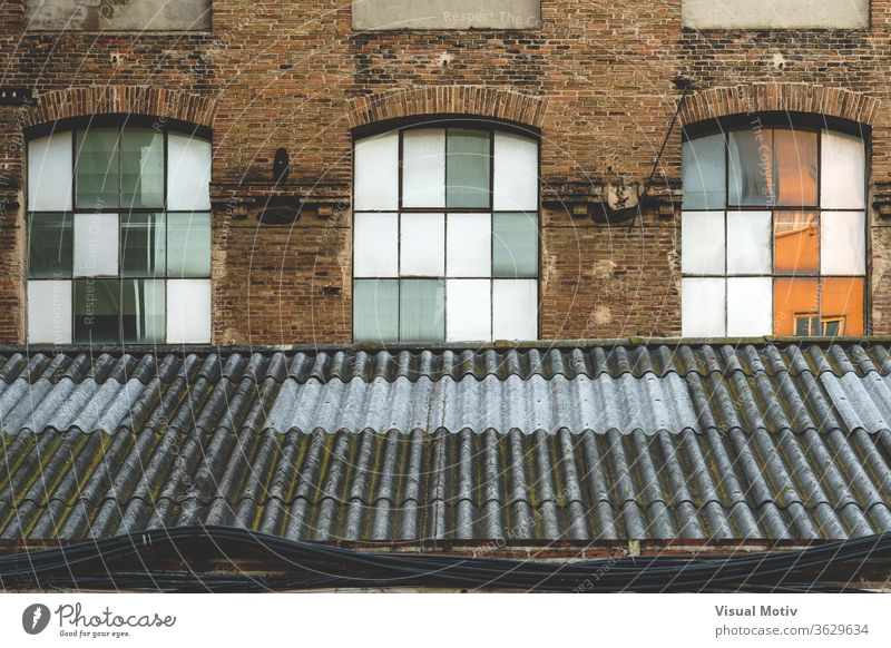 Windows and worn-out roof of an old abandoned textile factory at the afternoon light window building rooftop facade industry architecture architectural