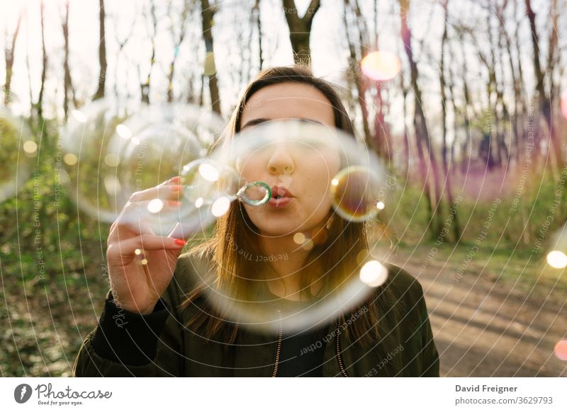 Young woman blowing soap bubbles in the woods. connect networking freedom day natural pretty forest portrait colorful share vision sharing outdoor happy