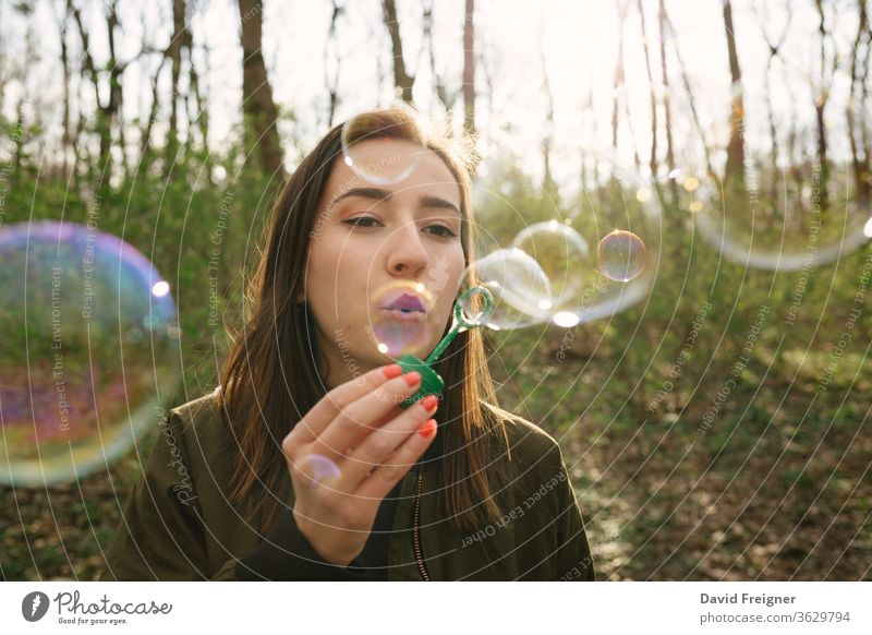 Young woman blowing soap bubbles in the woods. freedom networking women people happy careless fun leisure forest connect vintage enjoyment share outdoor cute