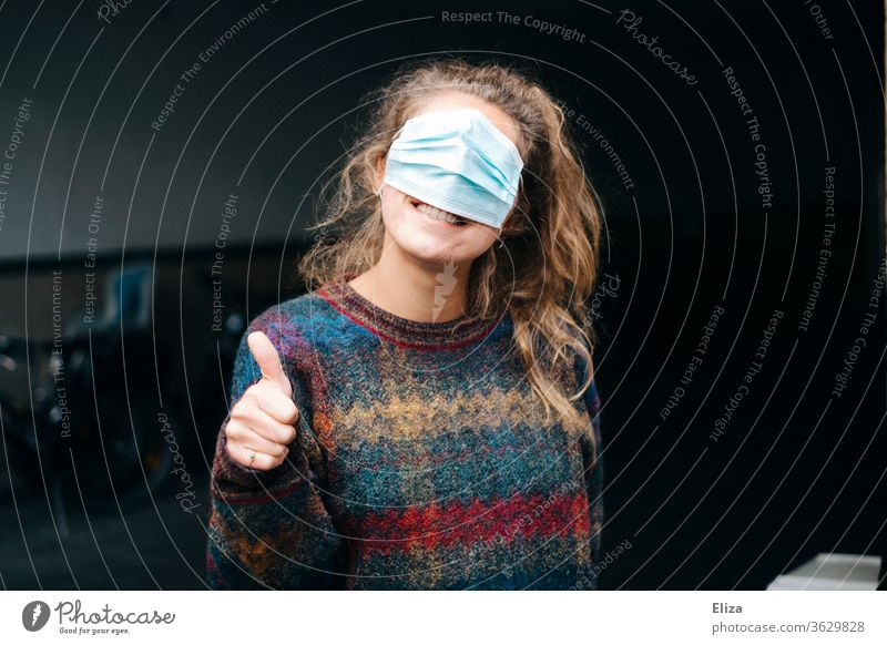Young woman with mouth guard over her eyes and thumb up Mask mns bunkum Laughter corona Protection False Alternative peer take hold of sb./sth. ironically fun