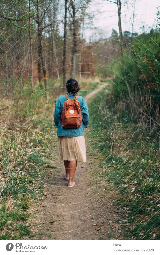 Woman from behind on a walk on a path through the forest Forest stroll To go for a walk Backpack spring Autumn Landscape Nature Going Lanes & trails Human being