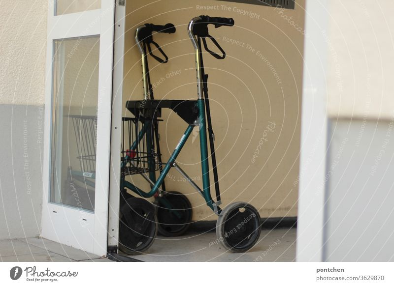 A rollator is placed in the entrance of an apartment building. Walker, aging. Rollator Walking aid age Entrance door Open Apartment house Senior citizen Healthy