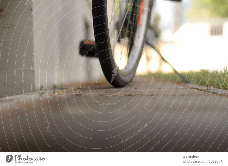 A bicycle stands in front of a house. View from below. Partial view. Tires, pedal, bicycle stand Bicycle Pedal Bicycle rack turned off Mobility Summer Sunlight