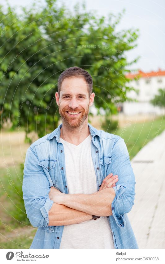 Casual guy relaxed in a park male young handsome casual man model beard fashion portrait denim attractive people adult person confident style enjoy shirt modern