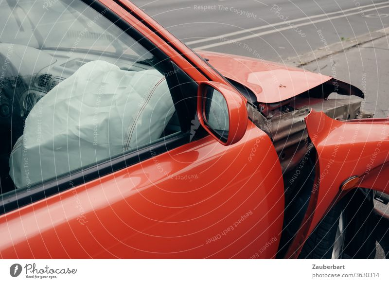 Airbag on the passenger side of a red car with dented fender Accident Red Front seat passenger Bulge Fender Total loss Street Road traffic Rear view mirror Tin
