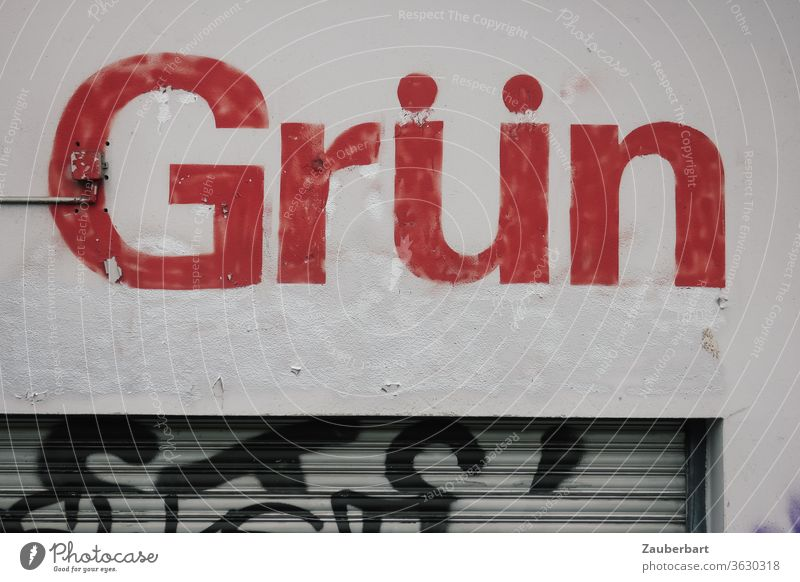 Green lettering in red letters on grey wall with blinds, paradoxical or contradictory green Red Letters (alphabet) Conflicting Disagreement Paradox