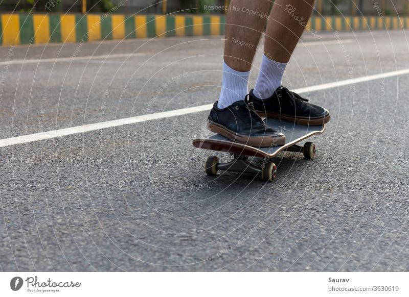 Close-up Shot of a Young Teenager's feet wearing Ripped Black Sneakers on his Skateboard cruising on an Empty Street while the White Line on the Road compliments his White Socks and also acts as a Leading Line in the Direction he is Moving.