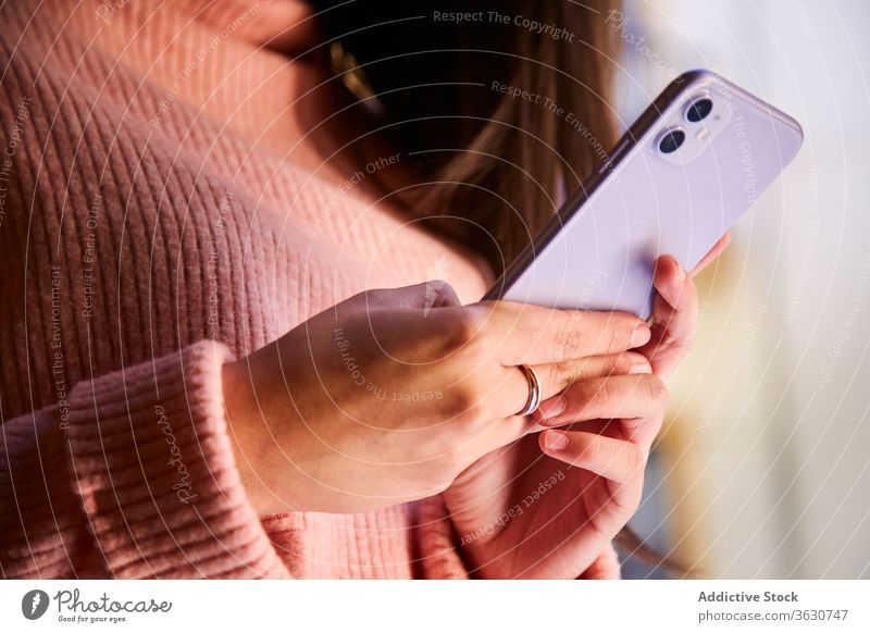 Calm woman browsing smartphone at home relax weekend calm harmony message using female charming device gadget rest window casual wear stand read cozy