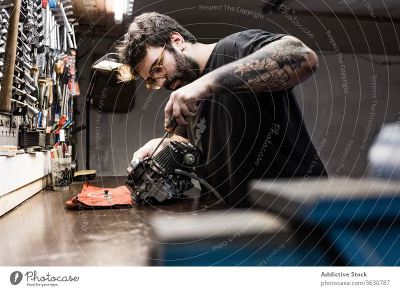 Focused male mechanic working in workshop repair master detail man vehicle workbench fix brutal side professional equipment tool garage occupation focus