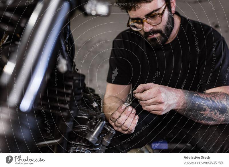 Bearded man fixing spark plug of motorcycle mechanic garage dirty motorbike male repair vehicle workshop serious maintenance service job transport equipment guy