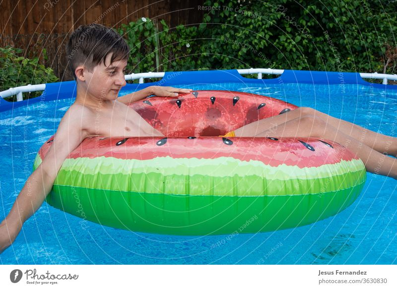 Boy relaxing in his swimming pool boy body caucasian blue adolescent bed dreaming enjoy exercise floating lying six teenage bath blond year active air bathing
