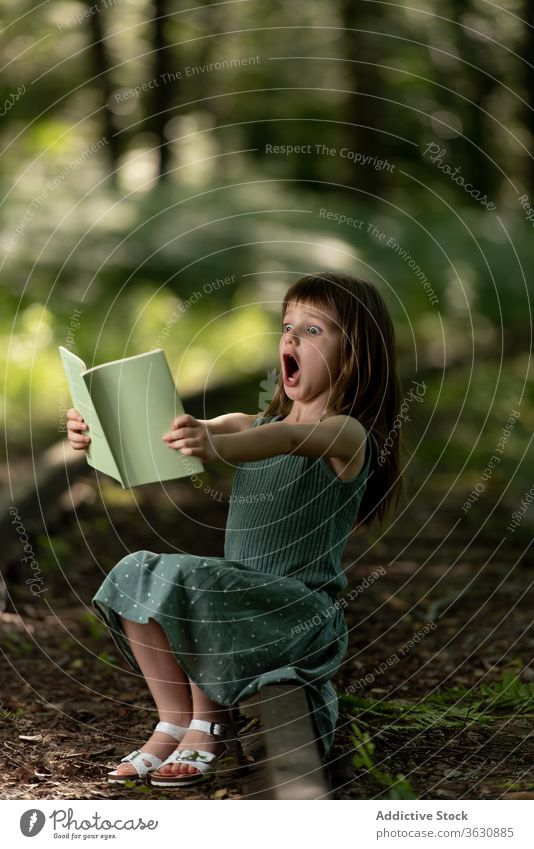Shocked girl reading book in park shock amazed astonish surprise wow preteen story interesting garden summer dress kid excited child adorable cute childhood