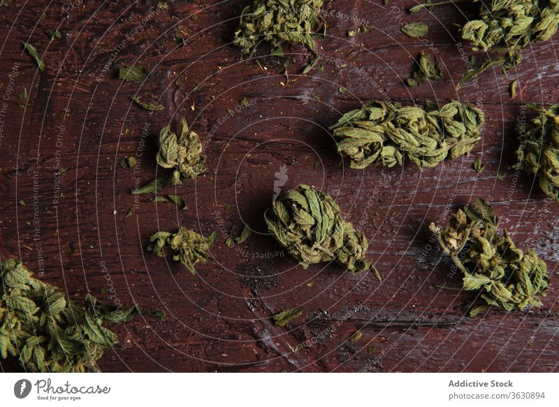 Dried cannabis buds on wooden table marijuana weed dried pile medical drug high relaxation dope organic natural plant bunch surface botany many illegal smoke