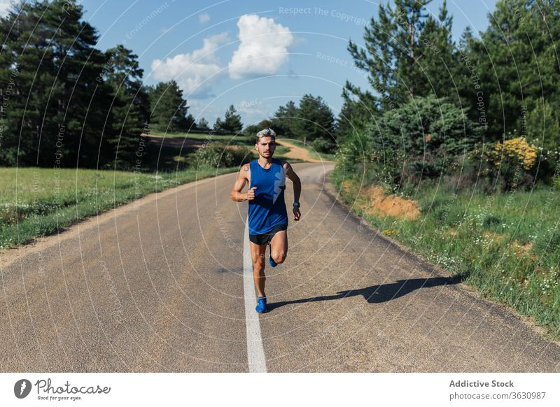 Determined man running on road during workout training fast exercise fitness young sport activity sportswear jog urban healthy body slim strong power