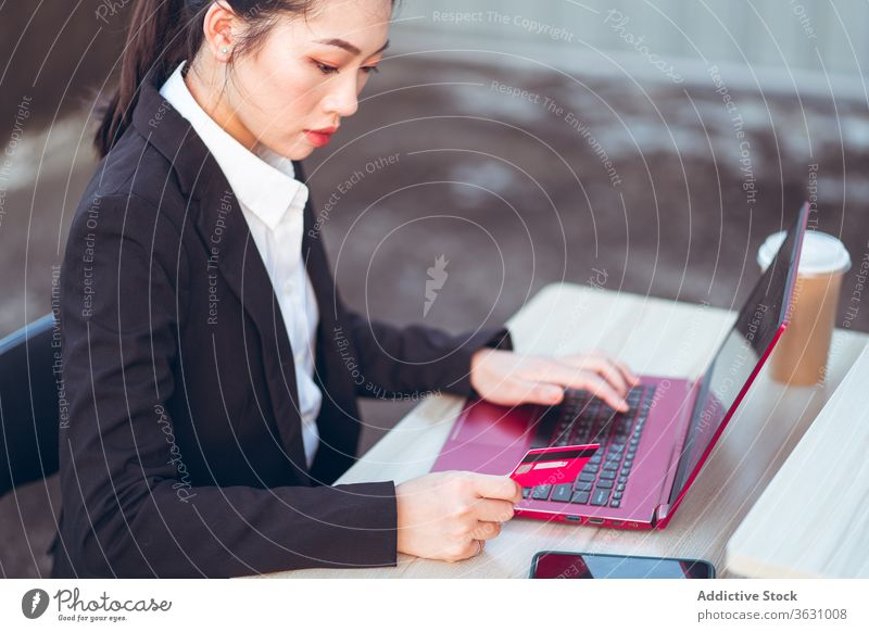 Young businesswoman making payment with credit card and laptop using busy smartphone online formal young asian ethnic serious gadget device female remote