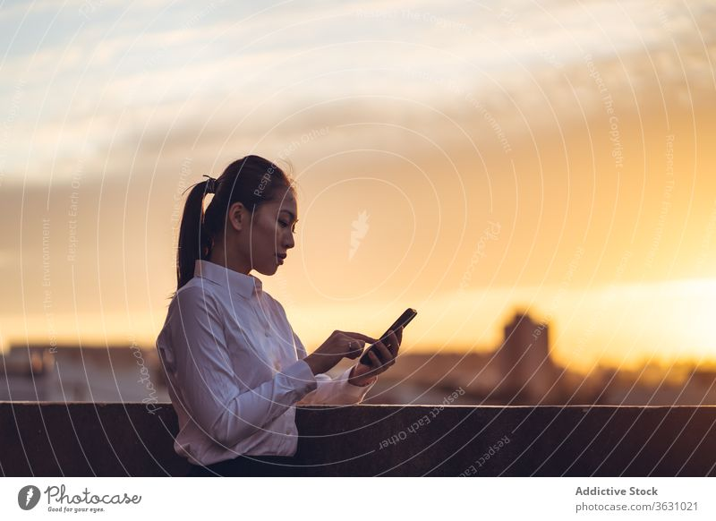 Young busy woman using smartphone on rooftop businesswoman serious focus message browsing young asian ethnic formal device gadget to go modern internet female