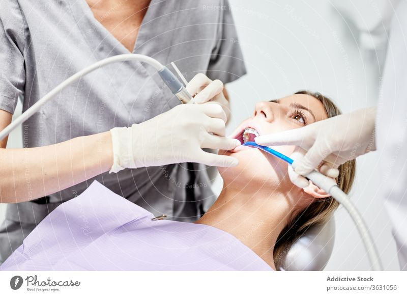 Crop anonymous dentist with assistant curing teeth of female patient cure check up clinic oral treat ejector salva hygiene professional client stomatology visit