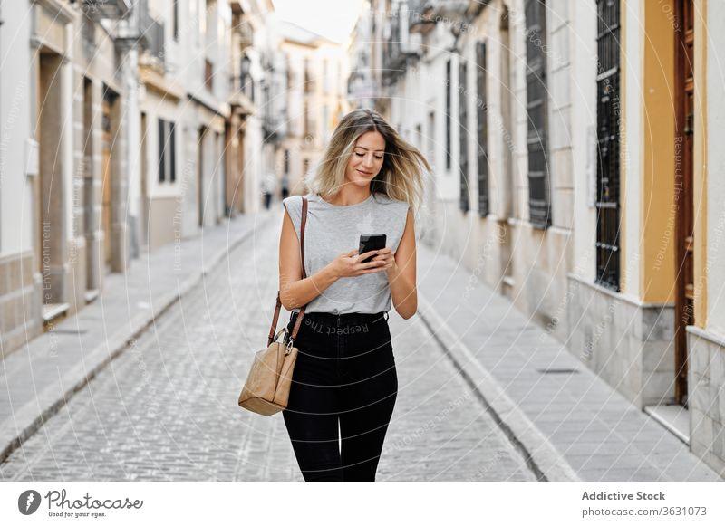 Positive young woman with smartphone walking on street city using happy style message browsing female mobile lifestyle device gadget stroll urban smile trendy