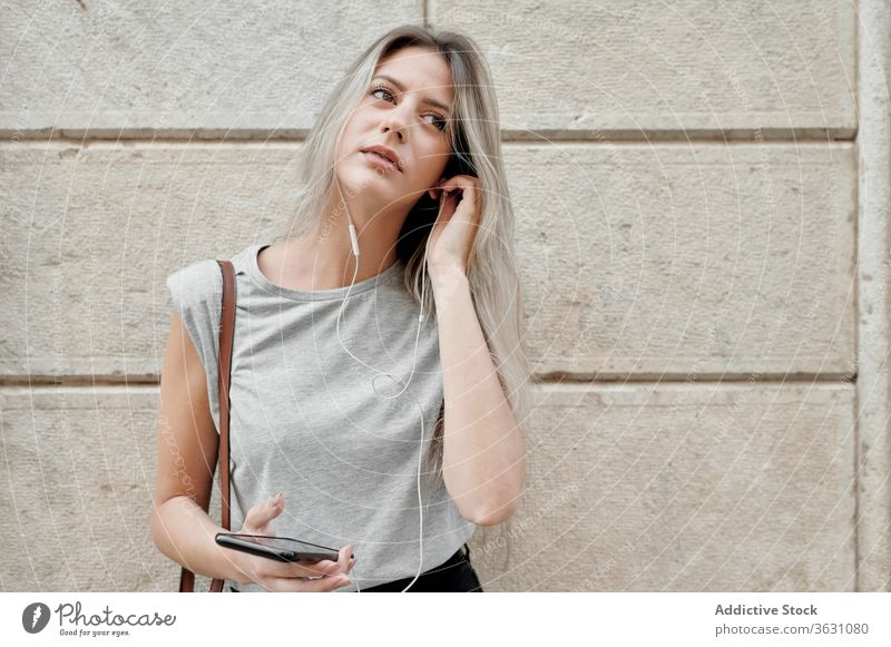 Woman with smartphone standing on street woman listen city using young happy style message browsing female mobile phone lifestyle device gadget music urban