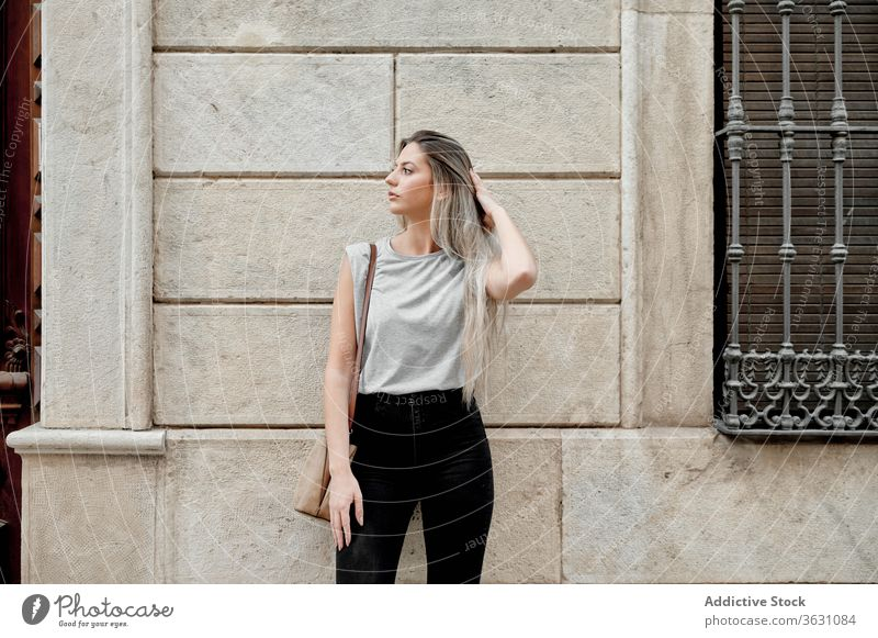 Woman standing on street on concrete wall woman city using young style browsing female lifestyle urban trendy lady millennial pedestrian building content