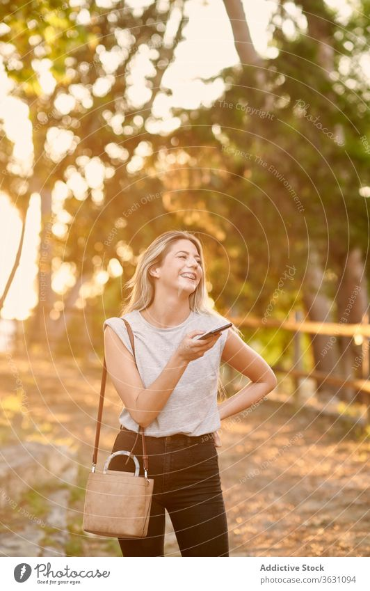 Happy woman with smartphone standing in park cheerful using happy enjoy browsing young female trendy lifestyle gadget device rest chill positive social media