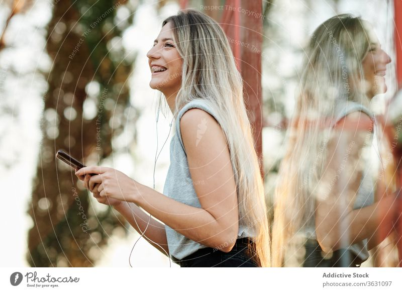 Cheerful woman with earphones using smartphone on street happy cheerful listen browsing young female music enjoy device gadget lifestyle smile online song