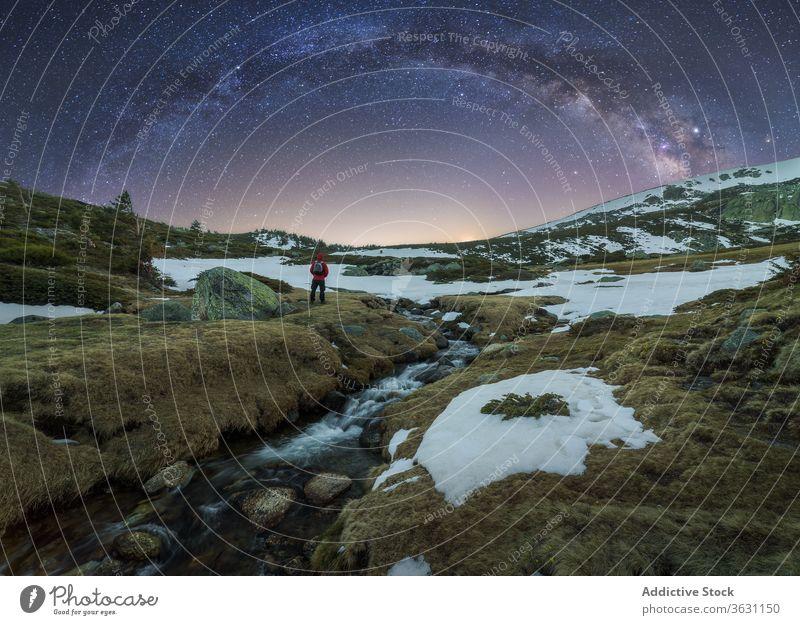 Traveler admiring view of Milky Way in mountainous terrain milky way traveler landscape sky twilight nature rough wild slope galaxy spectacular snow scenery